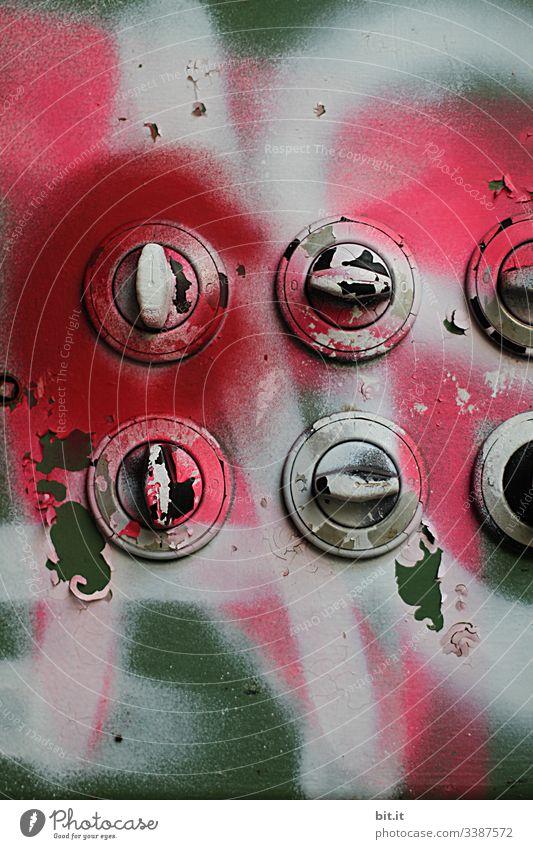 symmetrie l alte, besprühte, runde Drehschalter in leerstehender Fabrik. Wand mit Graffiti in pink & grün bemalt mit Lichtschaltern. Viele, alte, kaputte, angemalte, nostalgische Haustechnik, Lichtanlage, Schaltanlage mit runden Drehscheiben. Lost Place.