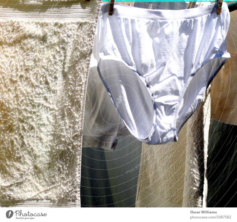 Waschtag im Hinterhof des Landes. Kleidung Linie trocknen Unterwäsche Sauberkeit Handtücher Baumwolle Schubladen Wäscheleine Wäscherei Außenaufnahme Farbfoto