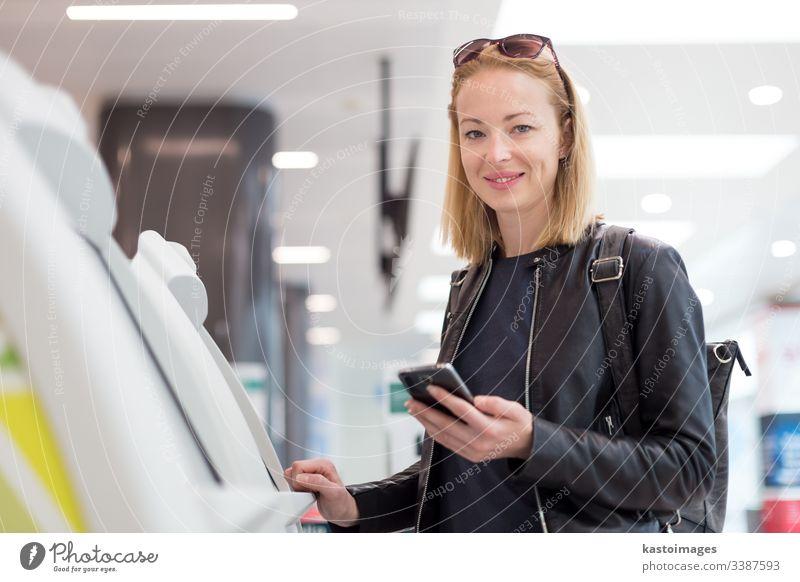 Lässige weiße Frau, die eine Smartphone-Anwendung und einen Check-in-Automaten am Flughafen benutzt, um die Bordkarte zu erhalten. Abheben Maschine Selbst