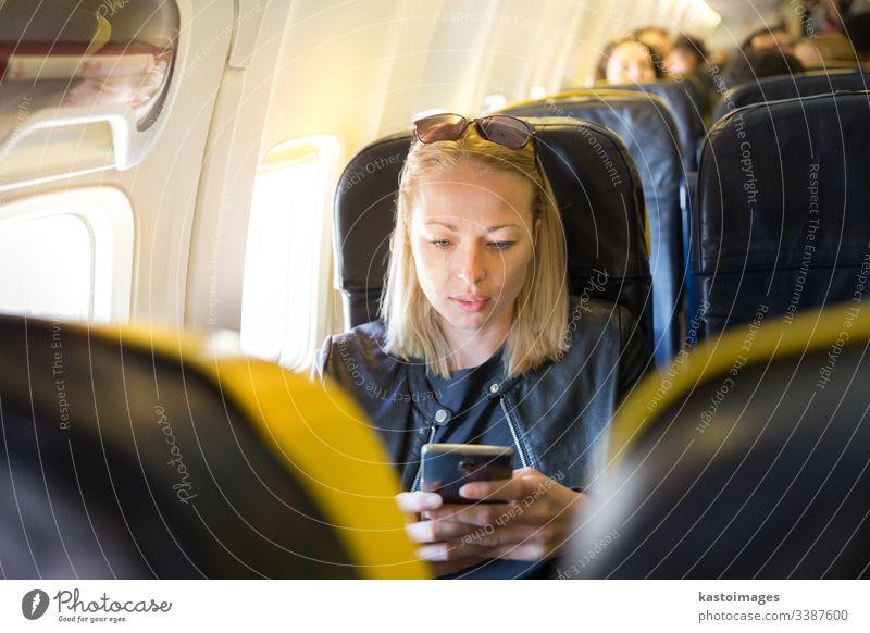 Frau, die während eines kommerziellen Fluges im Flugzeug das Mobiltelefon als Unterhaltungsgerät benutzt. Aussehen Ebene Blick Air Fluggerät Verkehr Transport