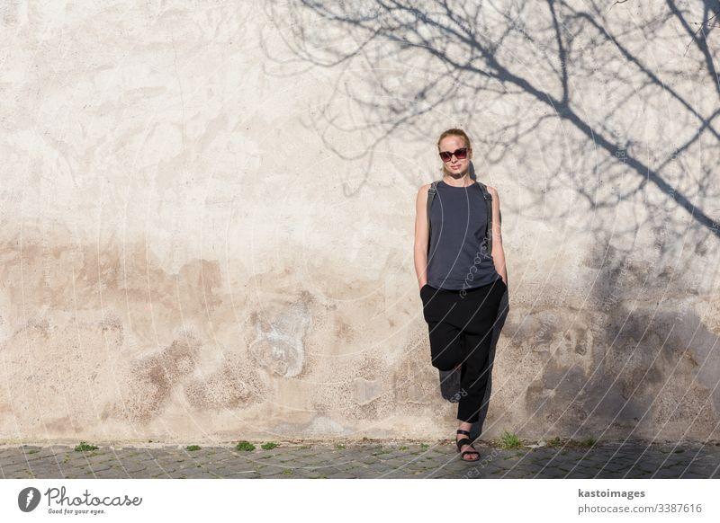 Grafisches und texturiertes künstlerisches Bild einer modernen, modischen Frau mit Sonnenbrille, die sich an eine alte, texturierte Retro-Wand lehnt, wobei der Schatten eines Baumes auf die Wand fällt.