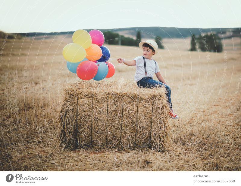 glückliches Kind mit Luftballons auf dem Feld Ballons Abenteuer entdecken Freiheit Korn Gras Wachstum Fröhlichkeit Glück Hut Selbstständigkeit Freude Lifestyle