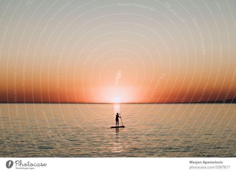 Frau paddelt bei Sonnenuntergang auf einem Brett auf dem Meer Aktivität Hintergrund schön Holzplatte Boarding genießend Abend Mädchen Harmonie Gesundheit