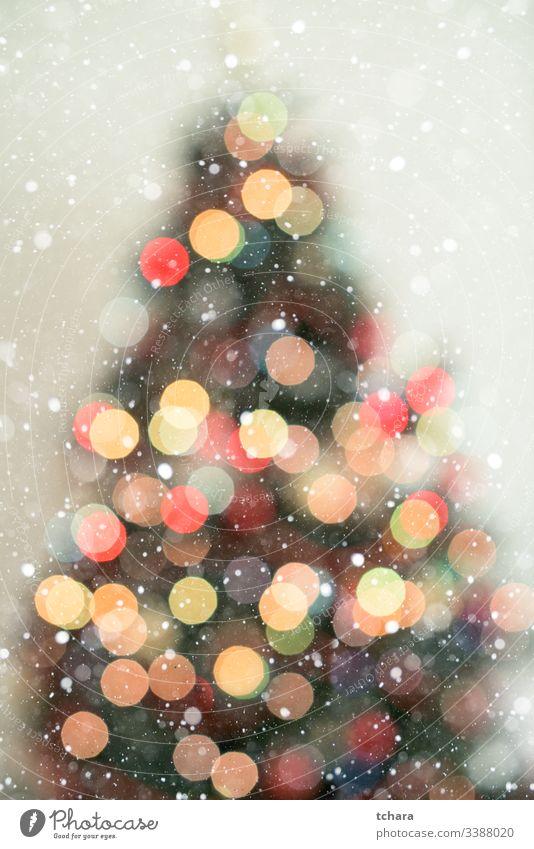Weihnachtsbaum in Bokeh im Hintergrund mit Schneefall Baum dekorieren festlich pulsierend Illumination lebhaft Zauberei u. Magie Schönheit feiern Formen