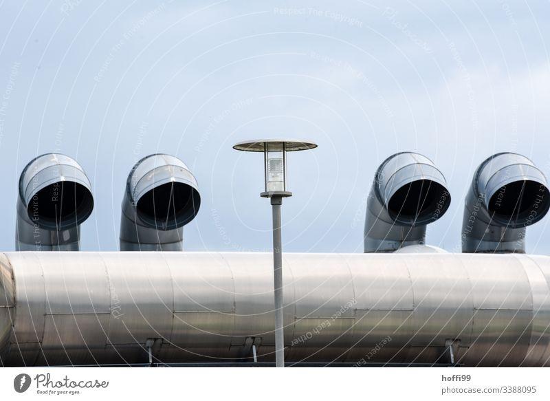 Vier Rohre für Abluft mit Laterne Lüftung Lüftungsschacht Laternenpfahl Metall Umweltverschmutzung Industrieanlage Schornstein Dach Fassade Gebäude Fabrik