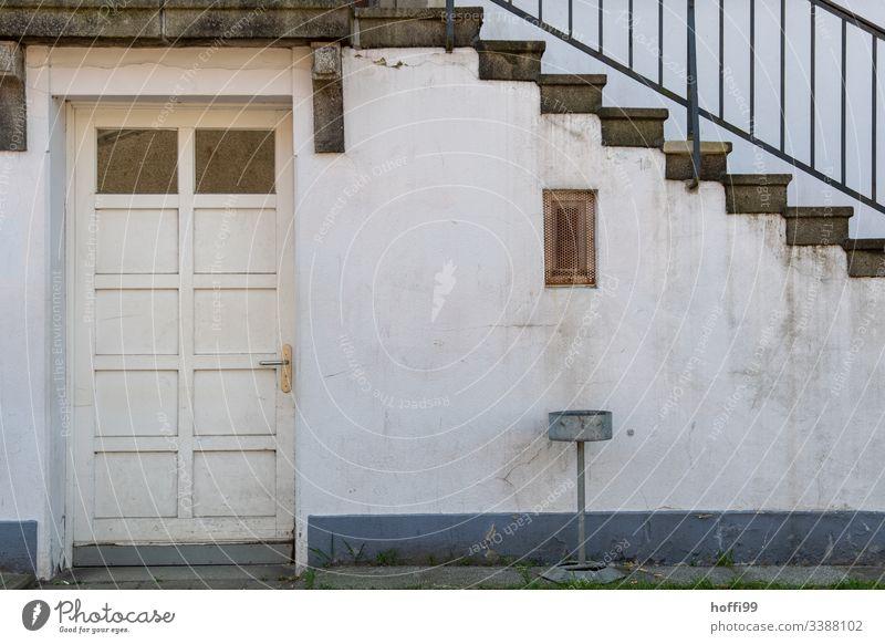 Treppe mit Geländer, Tür und  Aschenbecher vor dreckiger Wand diagonal Baustein minimalistisch Stufenordnung Treppenansatz Steinwand Ordnung Linien Muster
