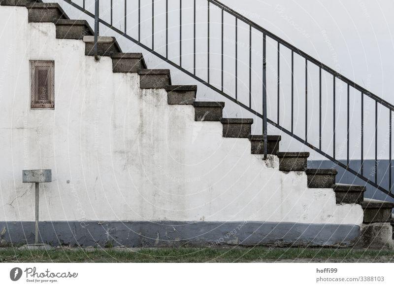 Treppe mit Geländer und Aschenbecher vor dreckiger Wand diagonal Baustein minimalistisch Stufenordnung Treppenansatz Steinwand Ordnung Linien Muster