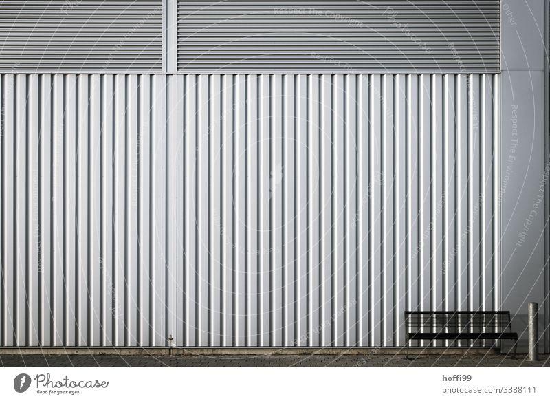 Bank mit Aschenbecher vor einer Metallwand - nehmen Sie Platz Industriebetrieb Wand Stahl Linie sitzen Mauer Architektur Fassade Strukturen & Formen