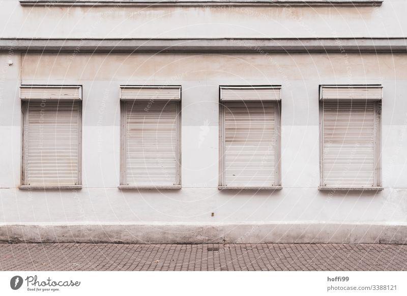 trostlose Außenfassade mit geschlossenen Jalousien grau trist Tristesse jalousinen Rollladen graue Wand schmucklos Einsam Depression depressivität Verlassen
