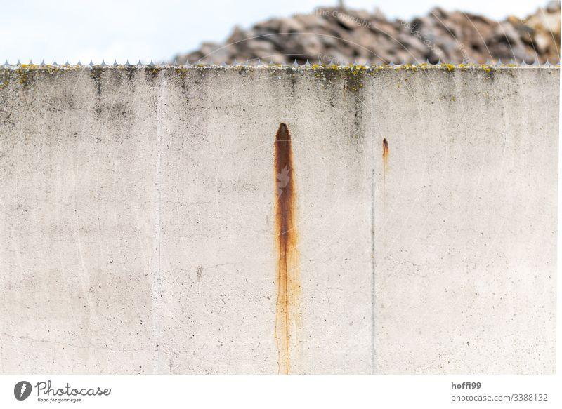 Rostspuren auf freigestellter Betonwand mit Dornenkrone rostflecken Rostflecke rostbraun Menschenleer geringe Tiefenschärfe geringe Schärfentiefe f1.4
