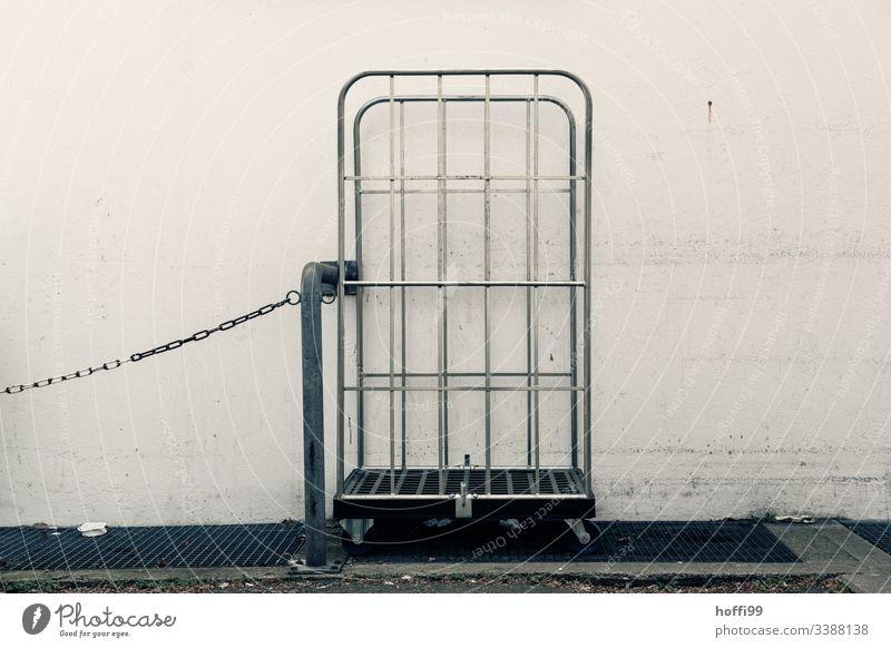 leerer Rollwagen mit Kette und Stahlrohr Lieferwagen grau trist Tristesse urban Außenaufnahme Menschenleer weiße wand Wand schmutz schmutzigweiß einfach