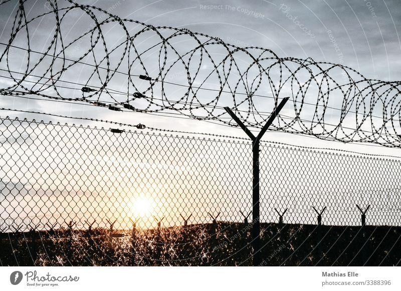 """Stacheldrahtzaun im Sonnenuntergang Flucht flüchtlinge flüchtlingshilfe Flüchtlingspolitik gitter Stacheldrahtzaun"""" absperrung Zaun Außenaufnahme Grenze"""