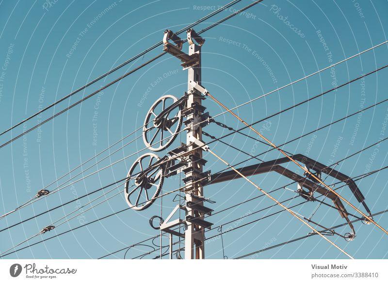 Oberleitung und Masten gegen den blauen Himmel Detailaufnahme Transportsystem Teil des Eisenbahnsystems Fahrleitungsnetz im Freien Außenseite industriell Pole