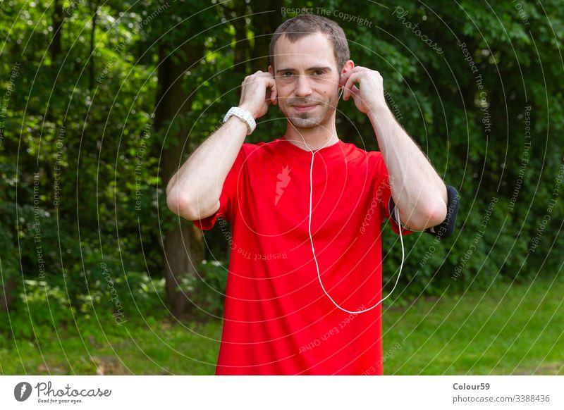 Junger Sportler mit Kopfhörern jung Musik Mann gutaussehend hören Training Übung Fitness Lifestyle Typ Gesundheit Telefon Athlet Erwachsener Aktivität im Freien