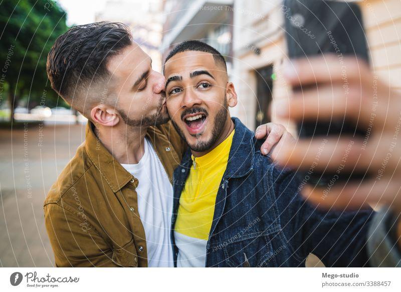 Ein schwules Paar, das sich auf der Straße vergnügt. Liebe Partnerschaft Handy Termin & Datum lieblich positiv Großstadt Freiheit Leben jung Stolz Selfie