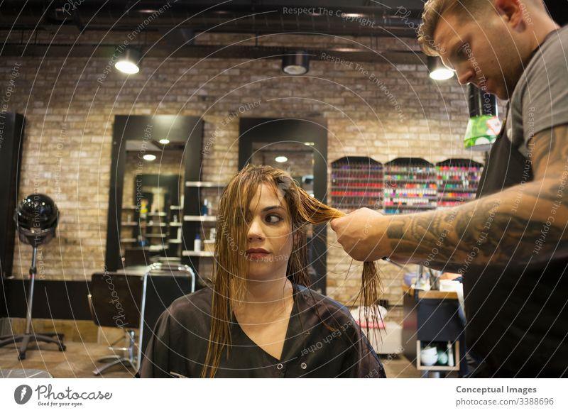 Kaukasische Frau lässt sich in einem hippen Friseursalon die Haare frisieren Themen der Friseurin verwöhnende Glamour-Haarpflege Haarschnitt Salon Hipster