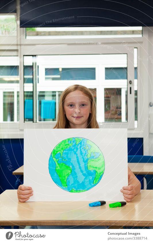 Kaukasisches Mädchen in der Grundschule hält ein Plakat mit einem Bild der Erde Zeichnung Planet Schulkind Umwelt Frau Kind Bildung Ökologie Zukunft Erhaltung
