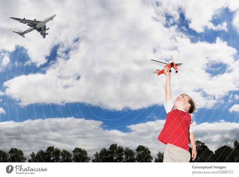 Junge Junge spielt mit einem SpielzeugflugzeugJunger kaukasischer Junge spielt mit einem Spielzeugflugzeug, während ein Passagierflugzeug über die Köpfe fliegtThemen der zukünftigen Phantasie Inspiration