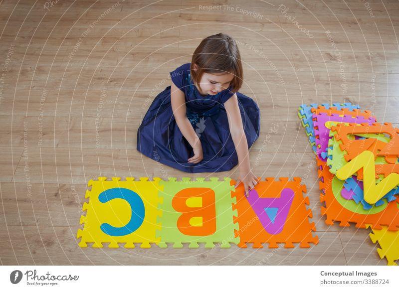 Ein junges Mädchen lernt das Alphabet abc Aktivität hell Kaukasier Kind Kindheit Farbe farbenfroh Konzept Textfreiraum kreativ Tochter Entwicklung Bildung Frau