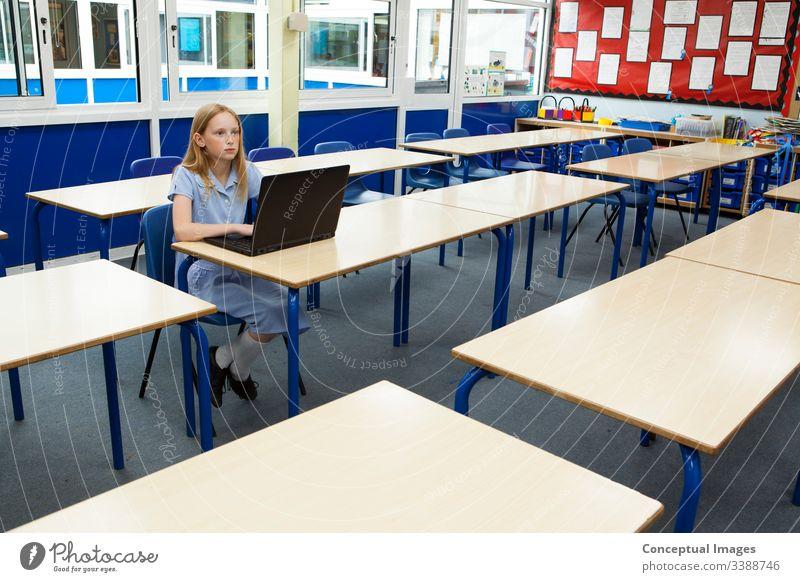 Kaukasisches Mädchen in der Grundschule mit einem Laptop in einem leeren Klassenzimmer schulisch Kaukasier Kind Kindheit Klassenraum Computer Datenverarbeitung