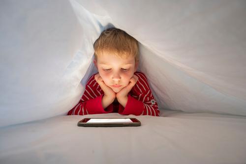 Kaukasischer Junge in seinem Bett, der mit seinem Smartphone einen Videoanruf macht, um mit einem Freund zu sprechen Kindheit facetime Mobile berühren