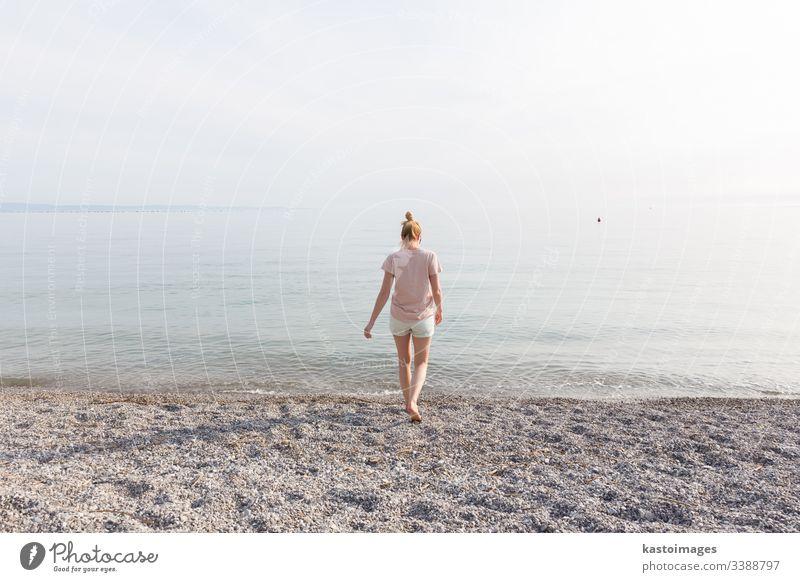 Fröhliche sorglose Frau genießt den Sonnenuntergangsspaziergang am weißen Pabbled Beach. Strand MEER Mädchen Glück Natur jung Sommer Wasser Meer schön Urlaub