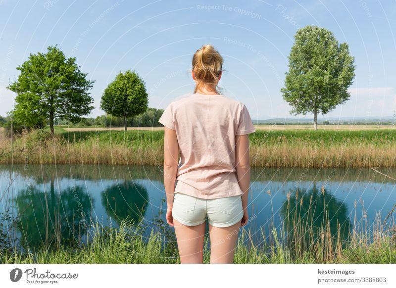 Junge Frau in lässiger Sommerkleidung, die eine schöne Aussicht auf die friedliche Landschaft genießt. Natur Wiese Rückseite jung Schönheit Tag grün Gesundheit