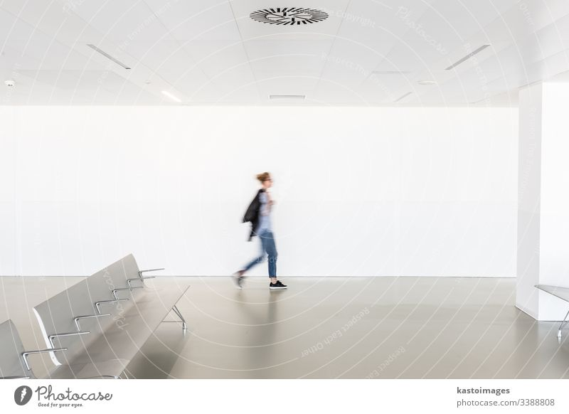 Bewegungsunschärfe einer Frau, die in einem zeitgenössischen weißen, leeren Flur geht Innenbereich Architektur Sitze Terminal modern Raum Kaukasier verschwommen