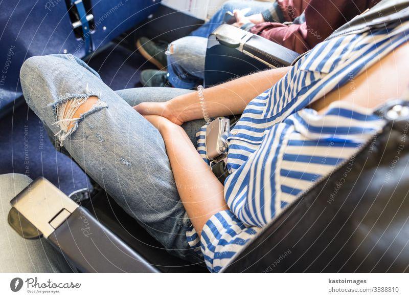 Weibliche Passagierin mit angeschnalltem Sicherheitsgurt, während sie im Flugzeug sitzt, für einen sicheren Flug. Sitz reisen Frau Fliege Verkehr Mädchen Ebene