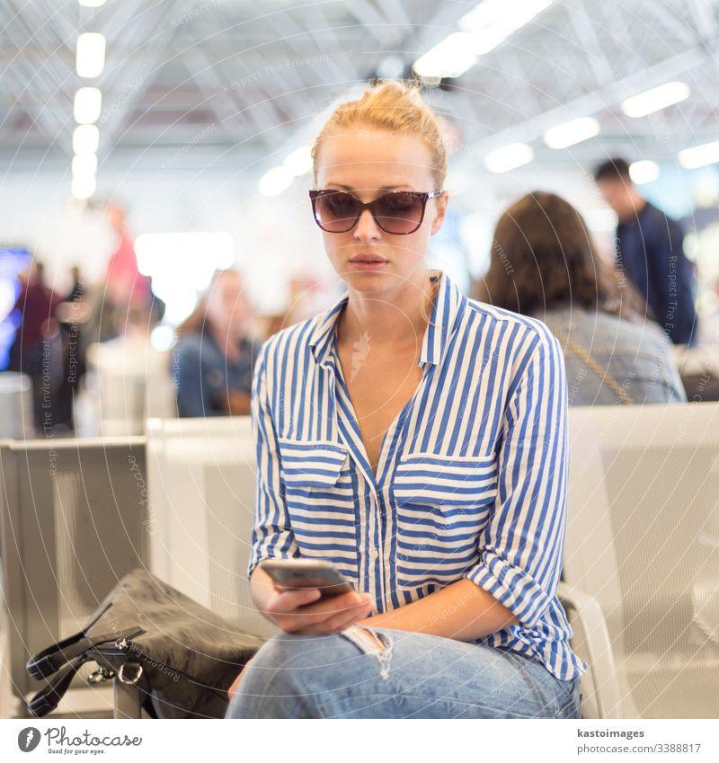 Frau benutzt ihr Handy, während sie an den Abfluggates des internationalen Flughafens auf das Einsteigen in ein Flugzeug wartet. reisen Sitzen Fahrkarte Telefon