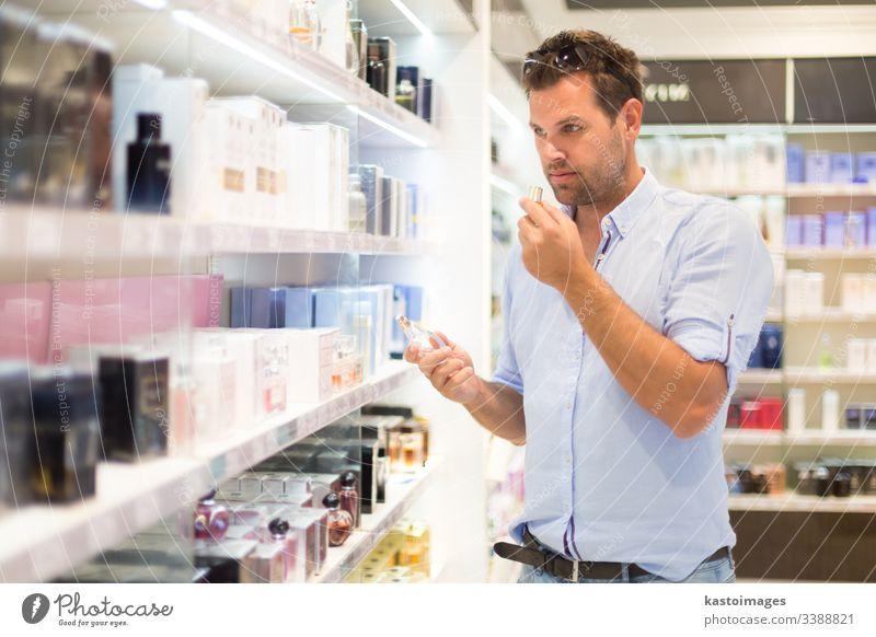 Eleganter Mann wählt Parfüm im Einzelhandel. Kunde Werkstatt kaufen Duftwasser Schönheit Laden Typ Kosmetik auserwählend Person attraktiv männlich Drogerie