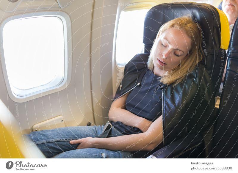 Müde blonde, lässige, kaukasische Dame, die auf dem Sitz schläft, während sie mit dem Flugzeug reist. schlafen Frau Ebene reisen Business Wirtschaft Stress