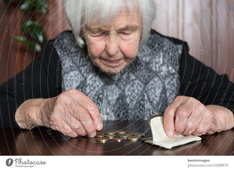 Ältere Frau, die am Tisch sitzt und Geld in ihrer Brieftasche zählt. Senior Rentnerin älter Armut Ruhestand alt leer Münzen Hintergrund unglücklich pleite