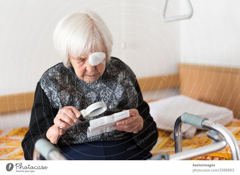 Sehbehinderte ältere Frau, 95 Jahre alt, sitzt am Bad und versucht mit der Lupe zu lesen. Senior Sehvermögen Augenlicht sehbehindert Rentnerin Pflege