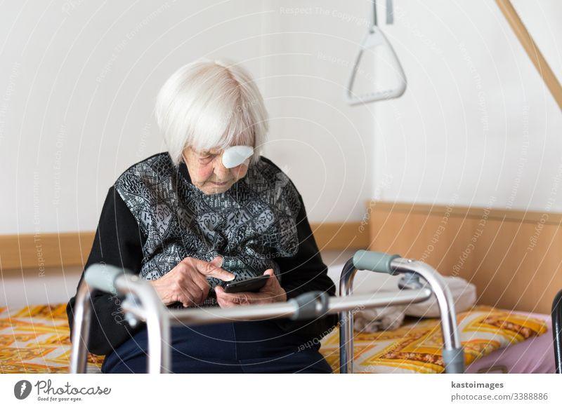 Einsame ältere Frau, 95 Jahre alt, die mit einem modernen Mobiltelefon am Schlechten sitzt. Senior Rentnerin Pflege Behinderung Krankenhaus Mobilität heimwärts