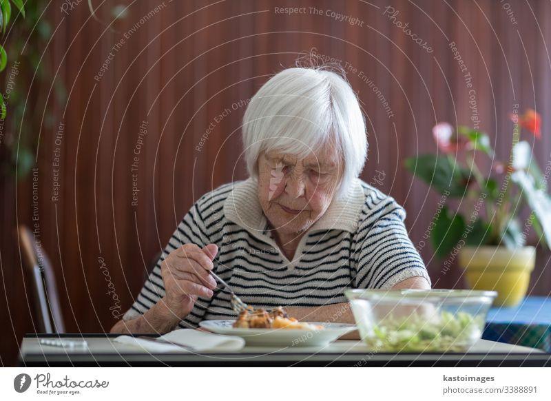Einsame ältere Frau, die ihr Mittagessen im Altersheim verzehrt. Senior Rentnerin Brieftasche Armut Ruhestand alt in den Ruhestand getreten Essen Großmutter