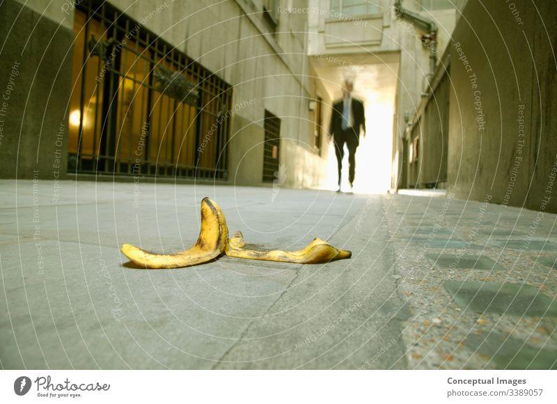 Niedriger Blickwinkel eines Geschäftsmannes, der auf eine Bananenschale zugeht Unfall Seien Sie vorsichtig. Business nachlässig Unachtsamkeit Vorsicht Konzept