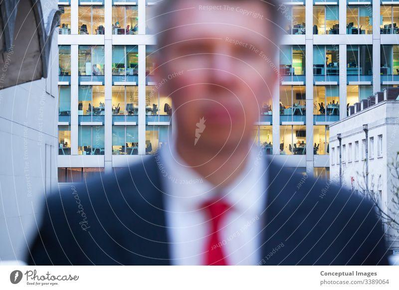Defokussierter Geschäftsmann, der in der Dämmerung in die Kamera schaut Erwachsener Nur für Erwachsene Business Geschäftsperson Großstadt Stadtleben Pendler