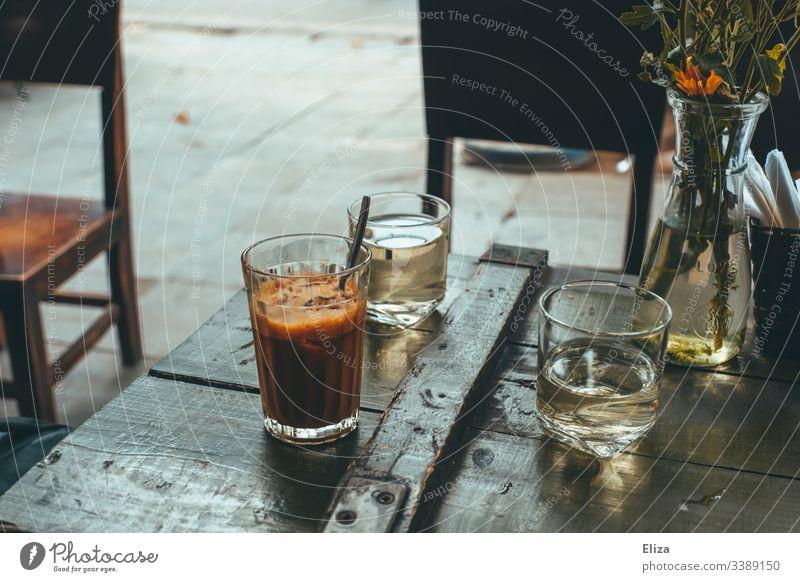Vietnamesischer Eiskaffee auf einem Holztisch in einem Café draußen in retro Farbgebung Kaffee holz kaffeepause aromatisch Morgen Getränk Koffein altehrwürdig