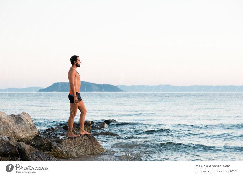 Junger Mann steht auf dem Felsen und genießt den Sonnenuntergang am Meer Erwachsener allein Hintergrund Strand Windstille Kaukasier Küste Abenddämmerung