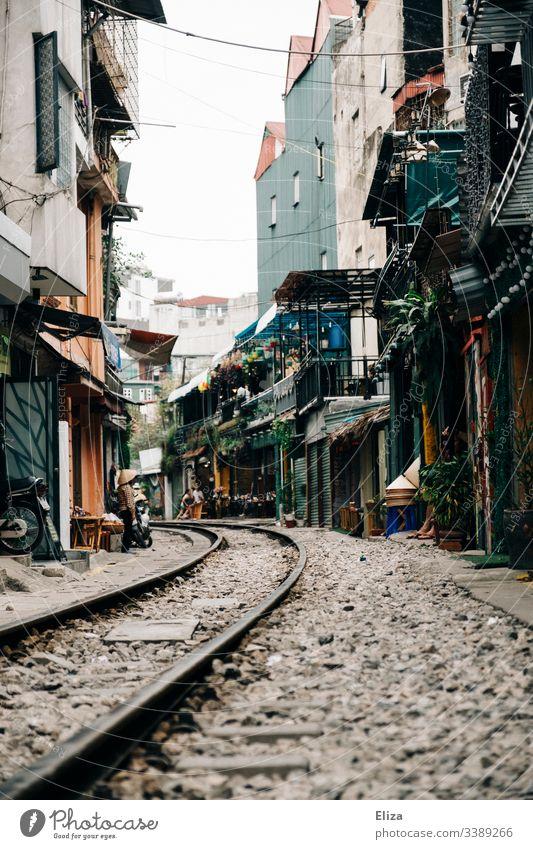 Die Sehenswürdigkeit Train Street in Hanoi; Zuggleise die durch eine enge Gasse, mit Wohnhäusern und Cafés führen Gleise Vietnam gefährlich Touristen wohnen