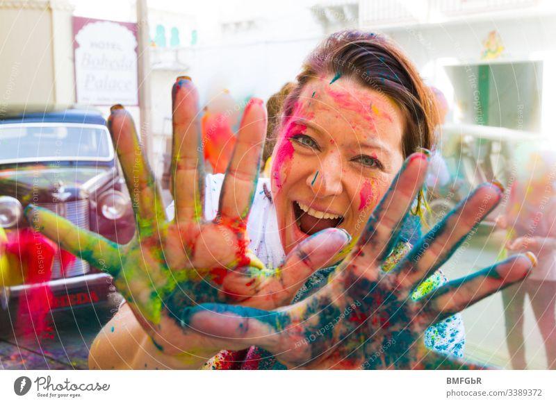 Frau, die sich am Holi-Festival amüsiert und ihre farbigen Hände in die Kamera zeigt aufgeregt verrückt genießend Fest der Farben Tourismus Konzept Fröhlichkeit