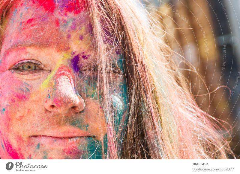 Porträt einer glücklichen Frau mit Farben vom heiligen Fest im Gesicht aufgeregt verrückt genießend Fest der Farben Tourismus Konzept Fröhlichkeit Sommer Spaß