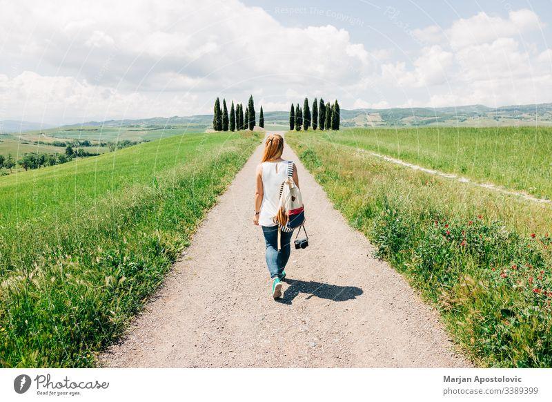 Junge Reisende zu Fuß in der Toskana schön Fotokamera lässig Land Landschaft Zypresse Zypressen Traumland genießend Europa Europäer Entdecker Frau Mädchen grün