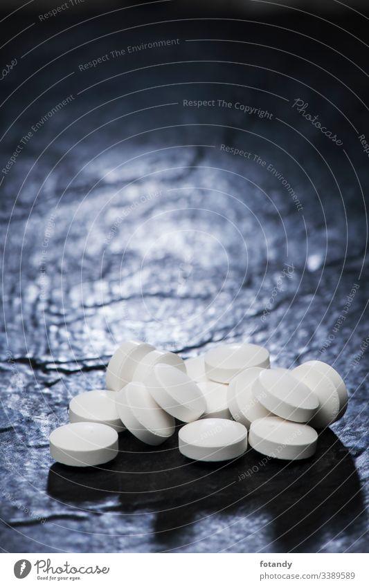 Anhäufung von Tabletten auf Schiefer vertikal Hintergrund Kapsel gepresst Darreichungsform Stillleben Vitamine heilen Objekt Medikament pharmazeutisch Apotheke