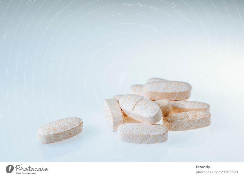 Group of elongated tablets with single tablet hintergrund Plastik Kapsel Gruppe Hartkapsel gepresst Darreichungsform Häufchen Stillleben Vitamine