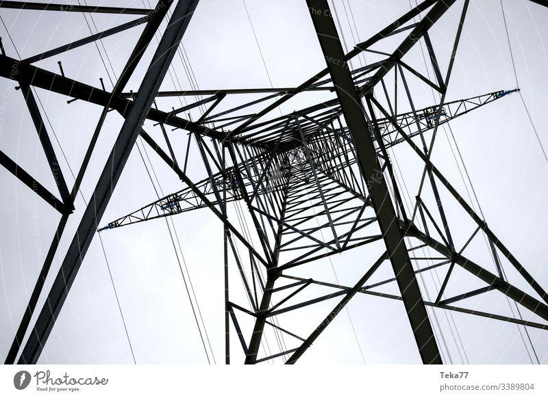 ein Strommast von unten horizontal Elektrizität Energie Kabel Hochspannung Energie-Transport Volt ampstorm Sonne Blitze Kraftwerk Stromkabel Farben Winter