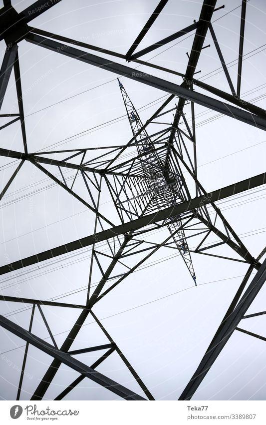ein Strommast von unten senkrecht Elektrizität Energie Kabel Hochspannung Energie-Transport Volt ampstorm Sonne Blitze Kraftwerk Stromkabel Farben Winter Himmel