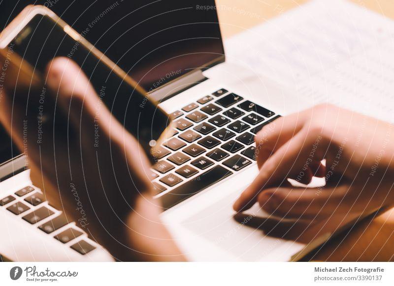 Mann, der am Notebook arbeitet und das Telefon in der anderen Hand hält Technik & Technologie Bildschirm Mobile Computer Business Laptop Internet Mitteilung