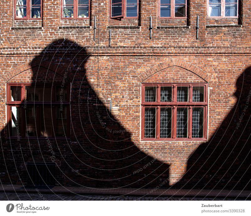 Fassade aus roten Backsteinen mit Fenster und Schatten eines gegenüberliegenden Hauses Wand ziegelrot Bauwerk Stein Textfreiraum unten Kontrast historisch